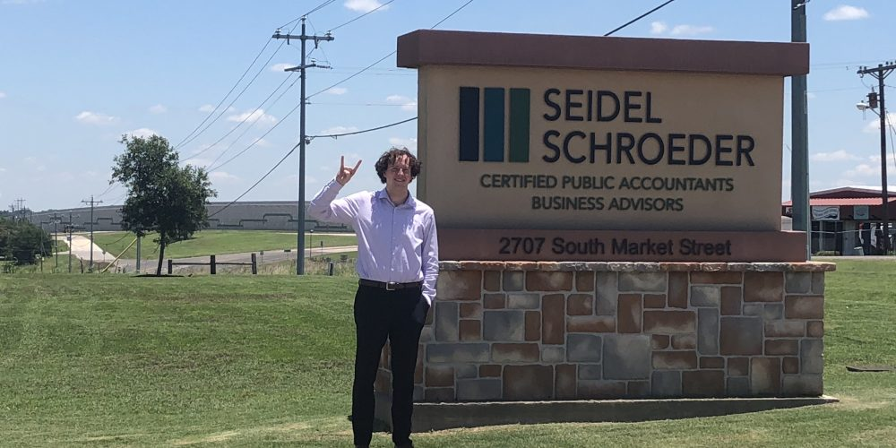 student holding hook em sign with hands in front of business sign in rural town