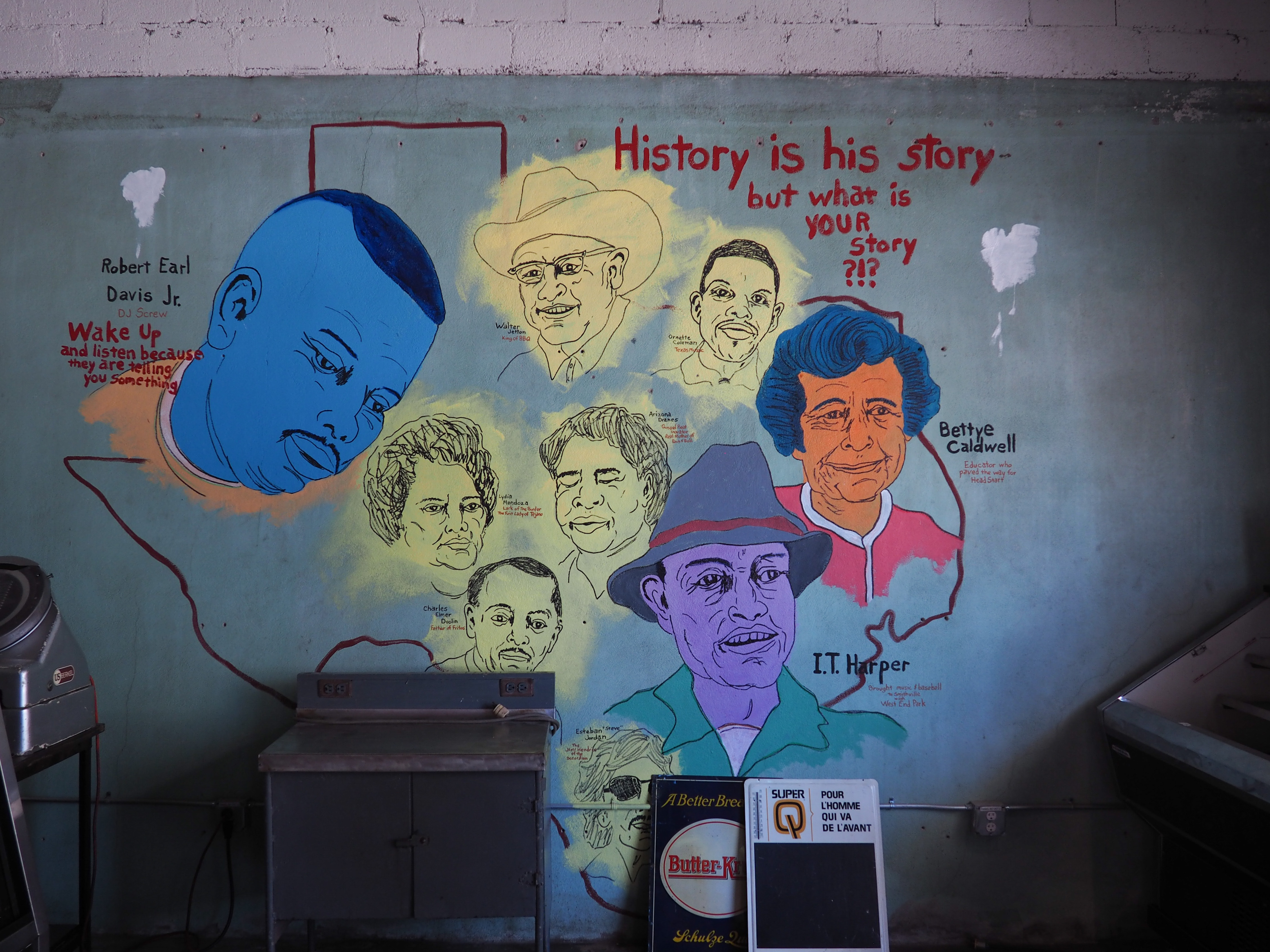 mural with various faces on side of building in rural town, Smithville, Texas