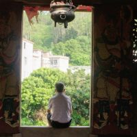 man sitting in temple doorway in rural China