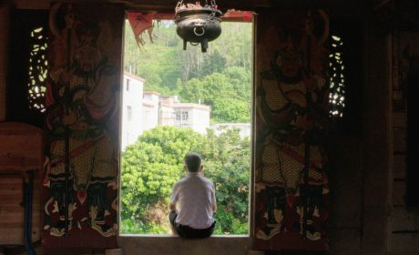 man sitting in temple doorway in rural China
