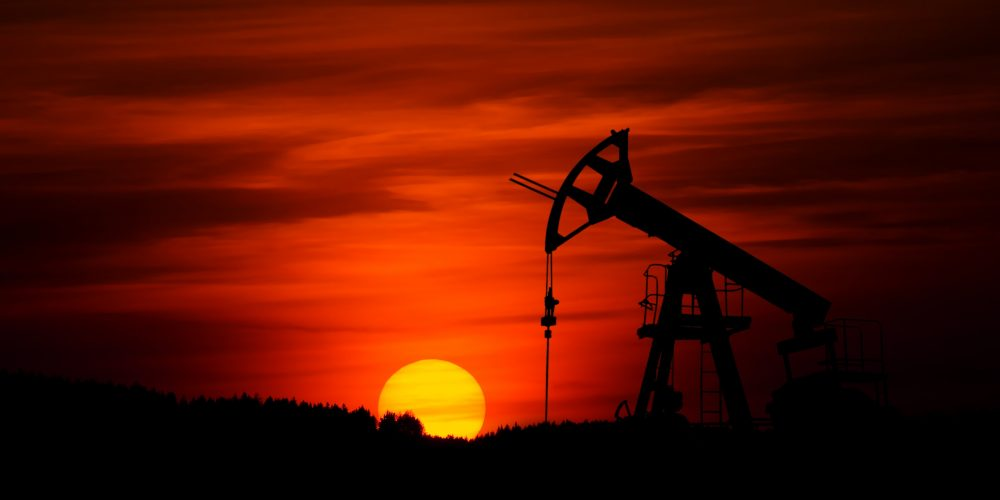 sunset behind oil and gas equipment