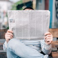 man sitting on a bench reading a newspaper