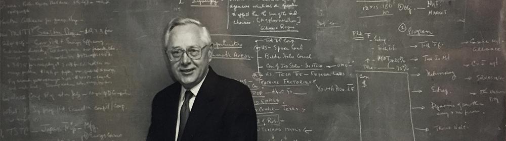 George Kozmetsky standing in front of chalkboard