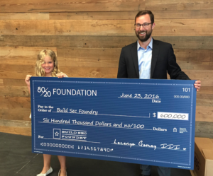 Sevi Bohn holds the $600,000 check from the 8020 Foundation with her dad Bart at the Build Sec Foundry launch.